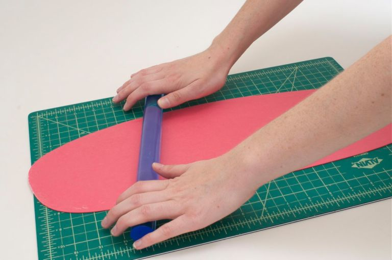 Roll out bright colored Satin Ice gum paste using a plastic rolling pin.