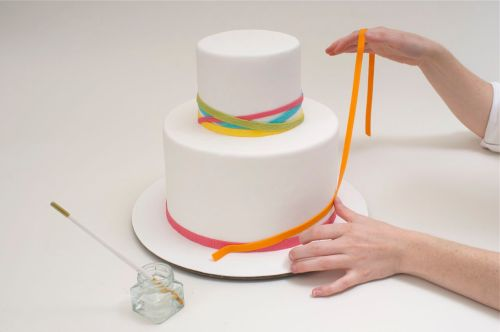 Apply bands to cake using water to moisten.  Play with colors, textures and angles to achieve the effect of festive streamers.