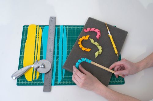 To make curly-cues, cut bright strips of colored paste in varying widths and lengths.  Wrap around any round objects, such as: pencils, drinking straws, wooden spoon handles, or paint brushes.