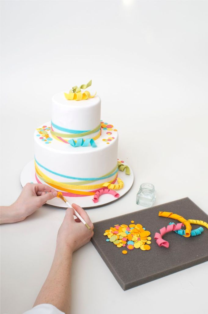 Attach curly-cues and confetti to cake with a dab of water.